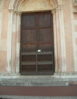 Feeling a little overwhelmed, Janelle poses by a church entrance, Montefalco